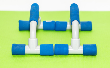 Plastic Push Up Training Apparatus On Green Fitness Carpet And White Background