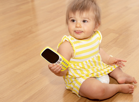 Beautiful Funny Eleven Monts Old Baby Girl In Yellow Dress Playing With A Mobile Phone Isolated On Wooden Background