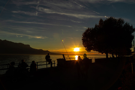 Sunset Silhouette. People near the Geneva Lake And Beautiful Sunset Over The Lake On The Background.