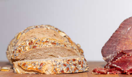Sliced beef ham on cutting board and bread with the grains. Beef ham and bread on wooden table. White background.