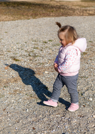 Beautiful 16 months old baby girl walking on the beach. Lake Leman near the Lausanne city. Switzerland Stock Photo