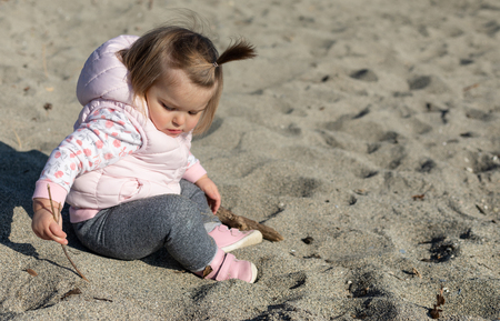 Beautiful 16 months old baby girl sitting on the beach. Lake Leman near the Lausanne city. Switzerland
