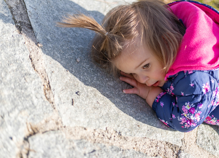 Sweet 17-Months Old Baby Girl Lying On The Stone Path. Outdoor And Head Photography