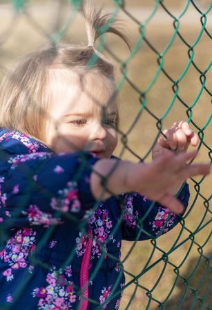 Sweet 17-Months Old Baby Girl Looking Through The Meral Fence. Outdoor And Head Photography Stock Photo