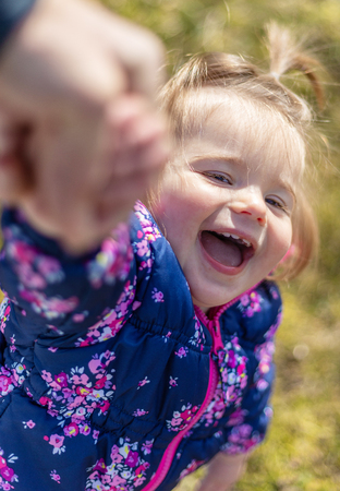 Sweet 17-Months Old Baby Girl Playing With Her Father. Outdoor And Head Photography