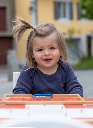 Nineteen monts old baby girl playing on the table with wooden toy. Outdoor photography