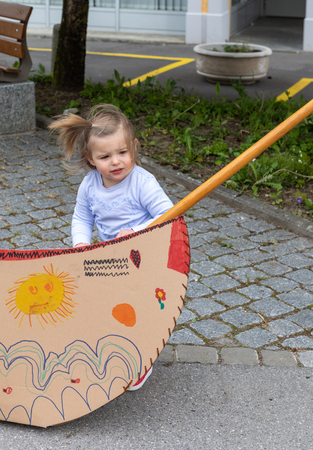 Nineteen monts old baby girl playing with the cardboard boat. Outdoor photography