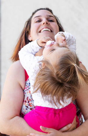 Portrait of loving mother who playing with her daughter. Awesome family moments. Outdoor photography