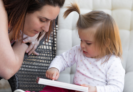 Mom and daughter reading a book on the terrace. Awesome family moments. Outdoor photography