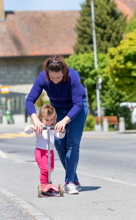 Mother teaching daughter to ride scooter. Awesome family moments. Outdoor photography