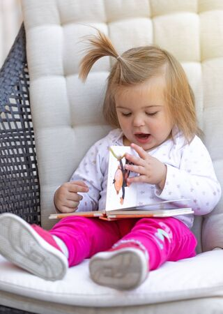 Sweet litlle baby girl sitting and reading the book. Outdoor photography