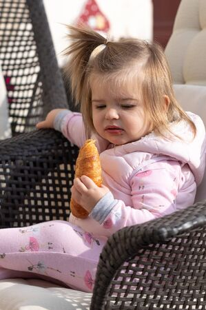 Beautiful baby girl eating the croissant in coffee shop. Breakfast time Stock Photo