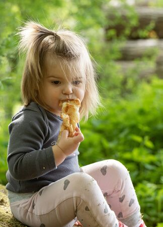 Beautiful baby girl eating the croissant in forest. Breakfast time Stock Photo