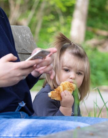 Mother and her daughter sitting in the park. Mother texting an message on smartphone,  girl eating croissant. Nature scene