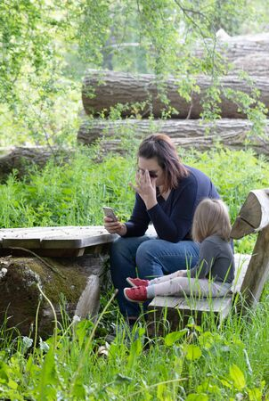 Mother and her daughter sitting in the park. Mother texting an message on smartphone. Nature scene Stock Photo