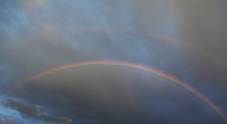 Two beautiful rainbows on the stormy sky. Darkness clouscape. Outdoor scene