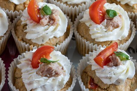Delicious cupcakes with cream, basil leaves, tomato slice and tuna fish. Food photography. Home made. Top view