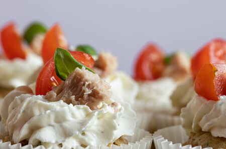 Delicious cupcakes with cream, basil leaves, tomato slice and tuna fish. Food photography. Home made