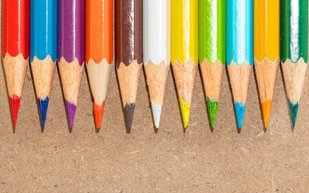 Wooden color pencils on a wooden background. Creativity and drawing equipment. Top view