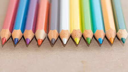 Wooden color pencils on a wooden background. Creativity and drawing equipment.