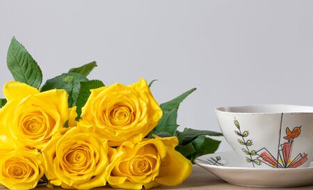 Beautiful bouquet of yellow roses with cup of coffee on a wooden table. Romantic scene Stock Photo
