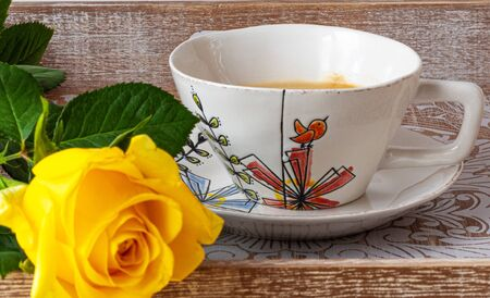 Beautiful yellow rose with cup of coffee on  a wooden table. Romantic scene