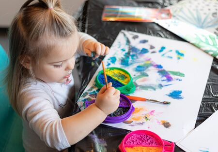 Portrait of cute little girl drawing at home with water colors
