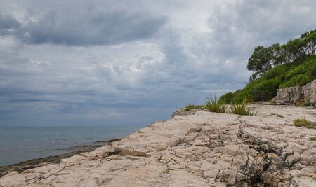 View on Adriatic sea at stormy day with big rocks. Region Istria, near the Rovinj city. Republic of Croatia