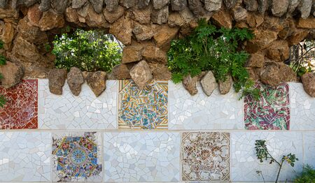 Details of trencadis mosaic of the ceramic and stone wall of Park Guell designed by Antoni Gaudi, Barcelona, Spain. Imagens
