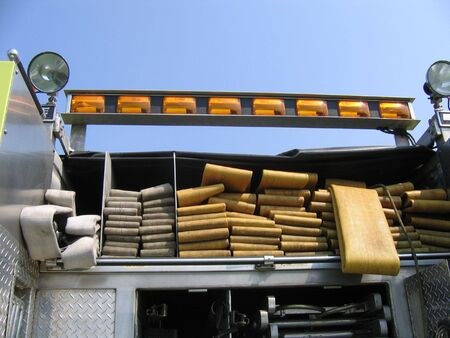 Hoses Stacked Up On The Back End Of a Fire Engine Banco de Imagens