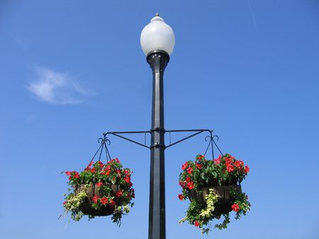 A Lamppost With Two Baskets of Flowers Against a Blue Sky Stock Photo