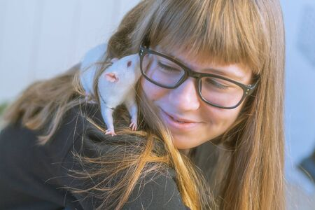 Teenage girl in glasses plays with white pet rat