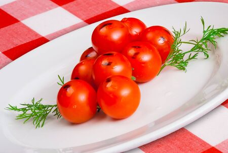 Grilled Piccadilly tomatoes with green vegetables on white plate closeup