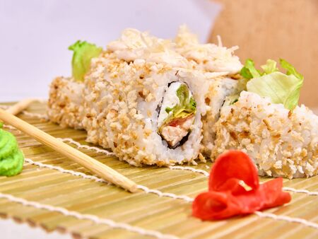 Set of Sushi rolls on bamboo mat with chopsticks