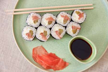 Fresh sushi rolls on a plate with soy sauce, mood shot