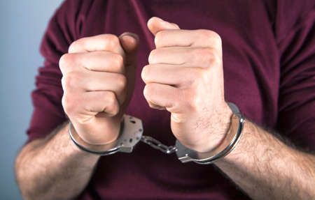 handcuffed man; prisoner