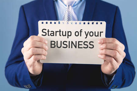 businessman holding a paper with the inscription startup of your business