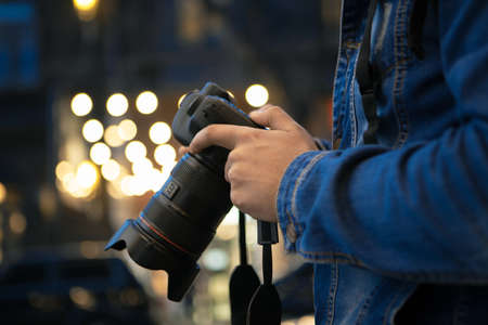 photographer with a camera on the background of evening street lights