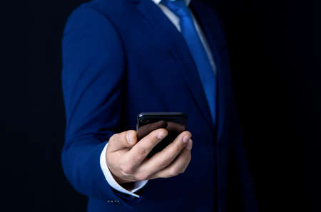 businessman in a suit on a dark background with a phone