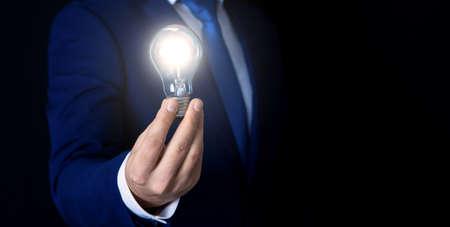 businessman holds shining light bulb, symbol of idea