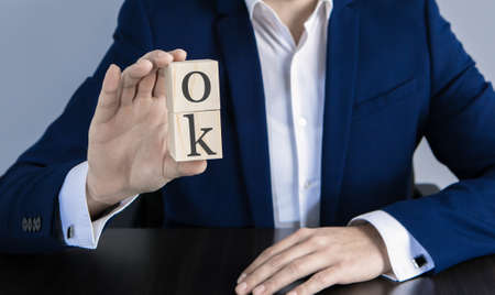 businessman holds in his hand a wooden cube labeled Ok