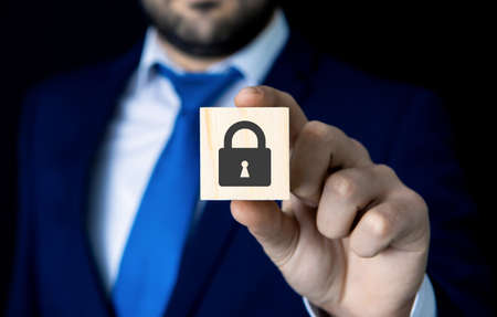 a businessman holds a padlock; security icon; business concept