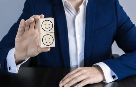 A sad and happy face is a wooden block in the hands of a businessman Archivio Fotografico