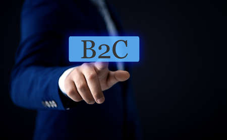 businessman on the touch screen with a finger clicks on the text B2C