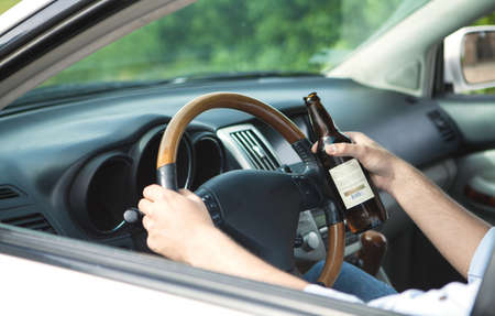 Drunk young man driving a car with a bottle of alcohol