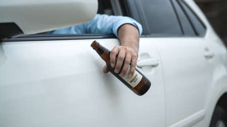 Drunk young man driving a car on the road holding a bottle of beer; Dangerous drunk driving 免版税图像