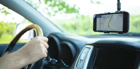 The driver uses a mobile smartphone with a GPS map navigation application.