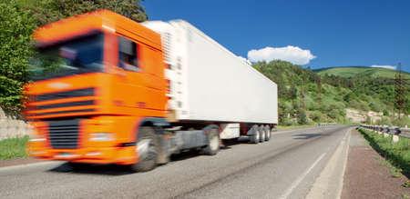 White truck arriving on asphalt road in rural landscape