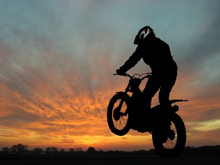Silhouette of motorcyclist in sunset landscape photo
