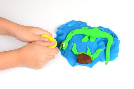 Mani di Bambina che fa i dinosauri dal variopinto impasto di argilla Archivio Fotografico - 32277178